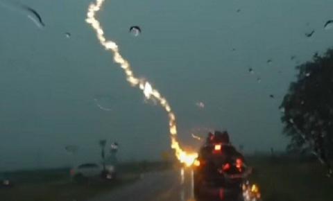 Câmera flagra momento em que carro com três crianças é atingido por raio