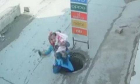 VÍDEO: Mulher se distrai com celular e cai em bueiro com criança no colo